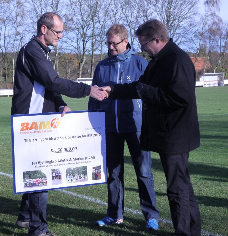 Dan Vestergaard fra BAM overrækker donationen til Kjeld Schytt og Niels Dueholm fra BIP